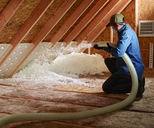 Man installing blown in fiberglass insulation in attic